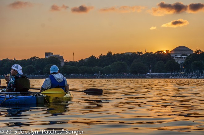 Kayakers watching the sunset over the MIT dome