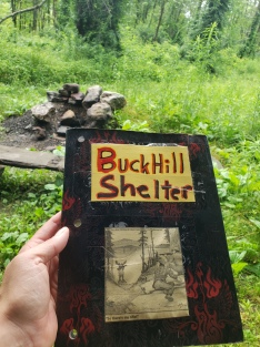 Sitting down to take a break and read the log book at Buck Hill Shelter