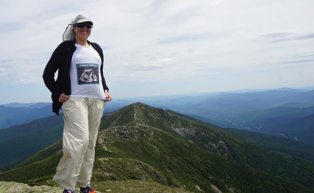 """Patches standing on top of Mt. Lafayette looking back at the ridge sporting a shirt that says """"Future Hiker"""" with a picture of the ultrasound of the baby girl I'm carrying with me everywhere I go."""