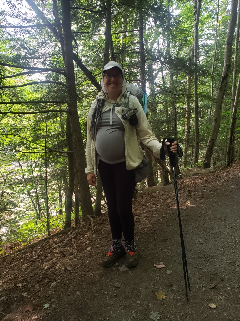 A happy pregnant backpacker with a full pacl.